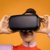 woman wearing VR headseat against orange background