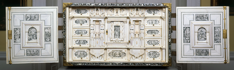 Frontal view of cabinet with doors wide open. All inner surfaces are covered with ivory inlays displaying monochrome scenes from the bible Book of Esther. The interior consists of multiple drawers and small cupboards.
