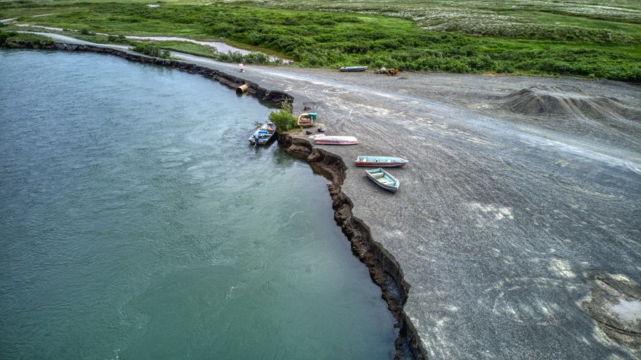 Aerial view of a gravel bar eroding into the river, with four boats at the erosion face.