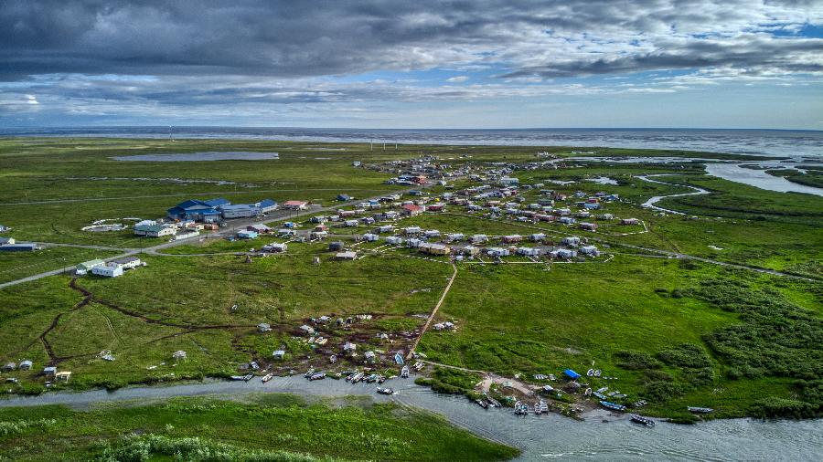 Aerial photograph of Quinhagak facing west, a Yup'ik community with dirt/gravel roads by the sea and Kanektok river, surrounded by lush green tundra in summer.